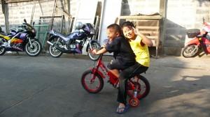 In Bangkok kunnen kinderen nog op veel plaatsen op straat spelen. Broer en zus hebben veel plezier, zo te zien.