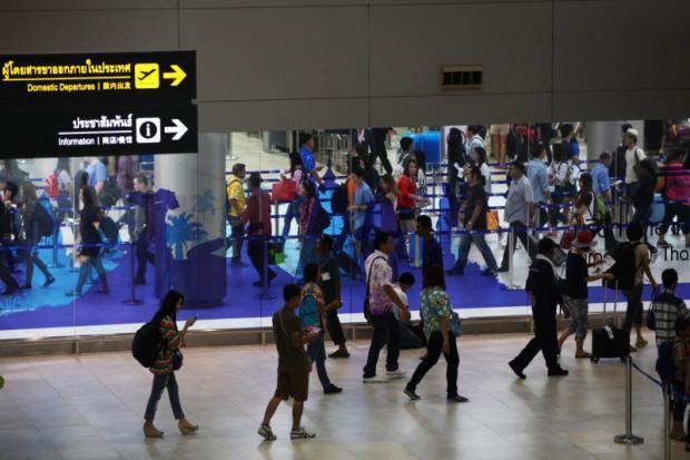 Passagiers lopen door een terminal van Don Mueang