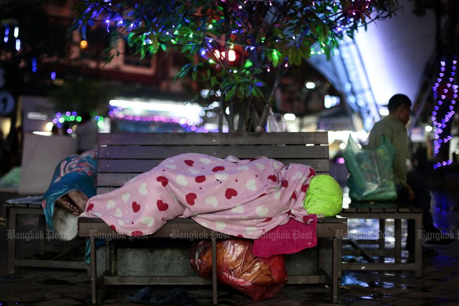 Dakloze bij Victory Monument, stevig ingepakt tegen de koude